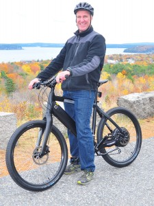 Joe Minutolo of the Bar Harbor Bicycle Shop pauses during a ride on an electric commuter bike at an overlook on the Acadia National Park Loop Road. PHOTO BY DICK BROOM